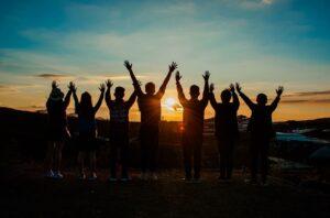 Silhuett av gruppe med mennesker i solnedgang
