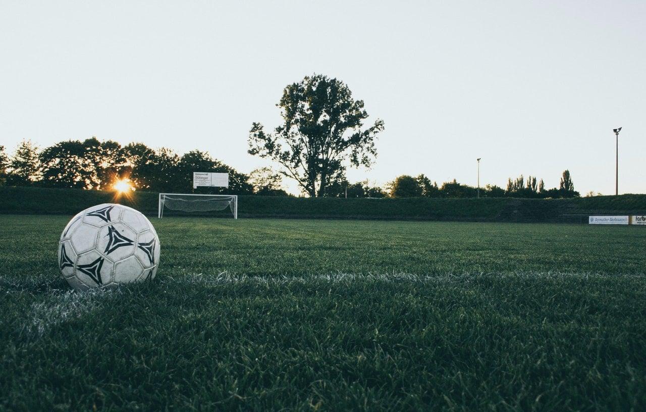 Svart og hvit fotball på fotballbane av gress