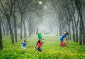 Barn leker med ball på gress