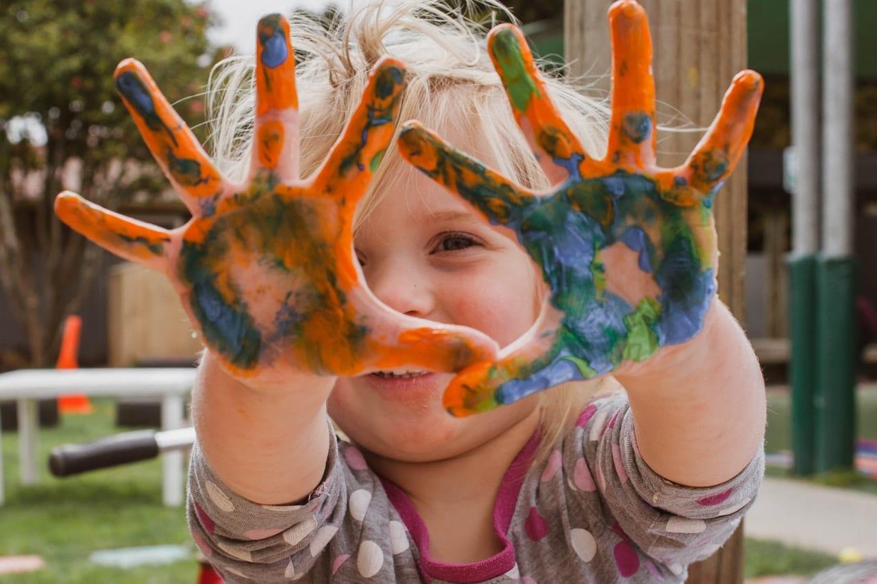 Smilende barn med hender dekket av maling