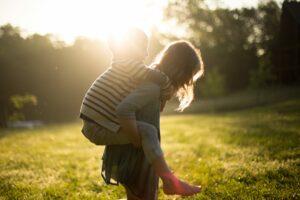 Barn som bærer et annet barn på ryggen